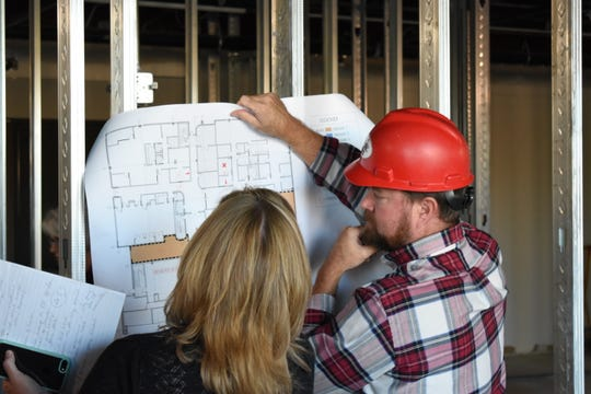 Phil Lash of Paul Construction goes through the floor plans for the Zanesville-Muskingum County Health Department renovation with Carol Howdyshell, the director of family and community health and wellness at the health department.