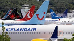 In this June 27, 2019 photo dozens of grounded Boeing 737 MAX airplanes crowd a parking area adjacent to Boeing Field in Seattle.