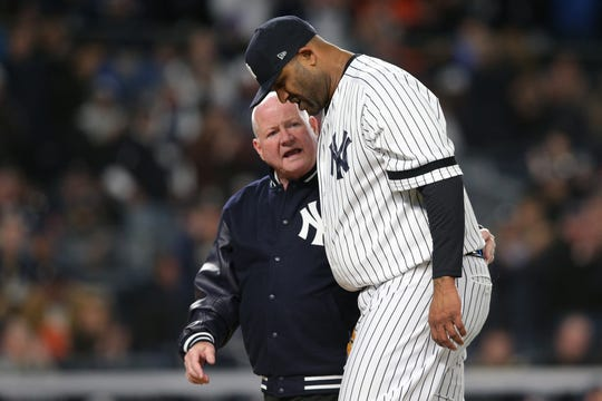 Yankees pitcher CC Sabathia walks off the field with trainer Steve Donohue.