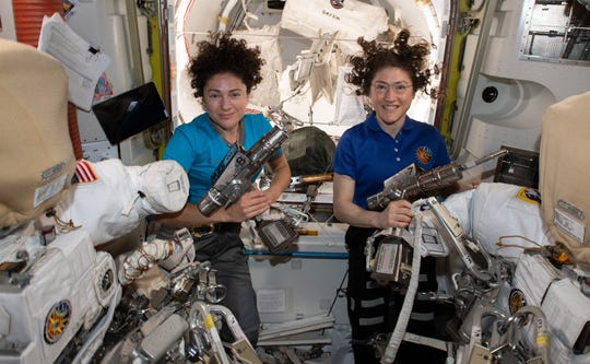 A handout photo made available by NASA shows NASA astronauts Jessica Meir (left) and Christina Koch (right) inside the Quest airlock preparing the US spacesuits and tools they will use on their first spacewalk together.