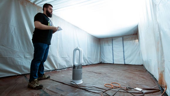 Lab tech Kyle Hamilton tests an air purifier in the 200 sq. ft. airtight room we built.