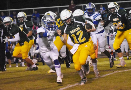 Holy Savior Menard quarterback Chris Canerday (12) runs for a gain against Red River in a home conference game Friday, Oct. 18, 2019. Red River won 33-27.