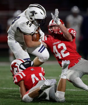 Kimberly's Deiondre Williams (44) and Zach Arent (42) tackle Appleton North's Cal Martine during an Oct. 18, 2019, game at Papermaker Stadium in Kimberly.