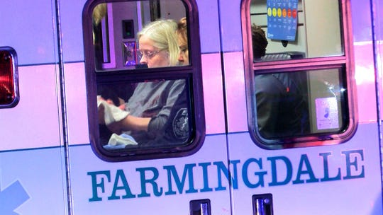 A woman wipes blood off herself in the back of a Farmingdale ambulance outside a Walnut Street home in the borough where a police officer was involved in a fatal shooting Friday night, October 18, 2019.