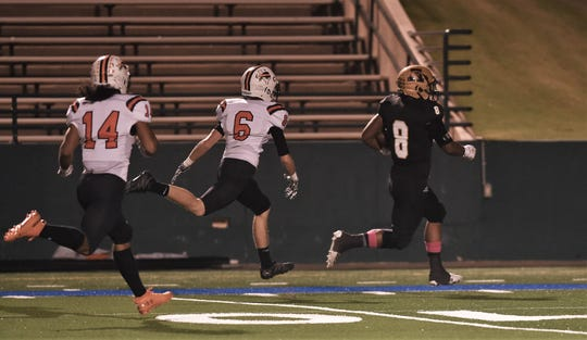 Phonzo Dotson scores on a 56-yard run early in the first quarter, beating Aaron Ellis (8) and Noah Roden (14) of Haltom to the end zone Friday at Shotwell Stadium. Dotson's touchdown gave the Eagles a quick 7-0 lead.