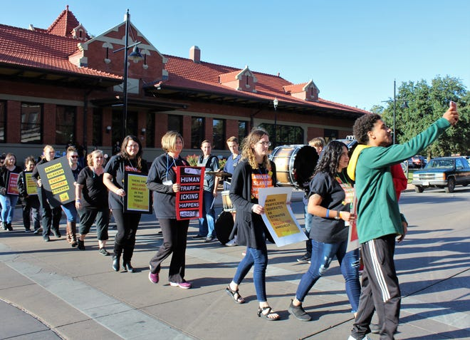 Stepping silently to the beat of several members of the Abilene High School drum line, Walk for Freedom participants begin a 14-block march Oct. 19 in downtown Abilene. Their signs spoke to their messages.