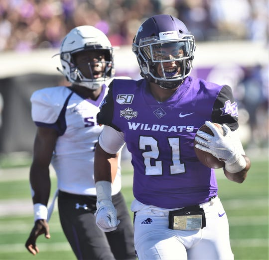 ACU's Tracy James (21) runs for a 3-yard touchdown as a Stephen F. Austin defender gives chase. James' TD tied the game at 7 with 10:11 left in the first quarter of the Southland Conference game Saturday, Oct. 19, 2019, at Wildcat Stadium.