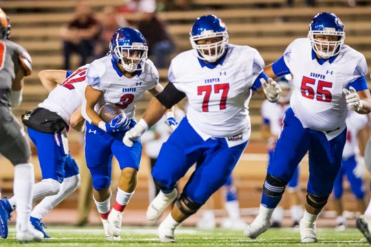 Cooper's Noah Garcia (3) runs the ball as linemen Devon Cosby (77) and Ryan Gofigan (55) block against Amarillo Caprock on Oct. 18 at Dick Bivins Stadium in Amarillo. Cosby is one of six Cooper seniors who will play at Hardin-Simmons in the fall.