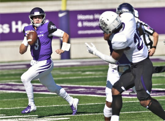 ACU quarterback Luke Anthony, left, looks for a receiver while under pressure against Stephen F. Austin during the Southland Conference game Oct. 19 at Wildcat Stadium.