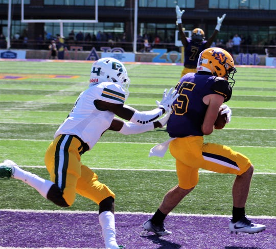 A teammate signals touchdowns after Hardin-Simmons' Gatlin Martin (15), a former Wylie Bulldogs standout, catches a 22-yard pass from Kyle Jones just before halftime to give the Cowboys a 35-0 lead Saturday over Belhaven.