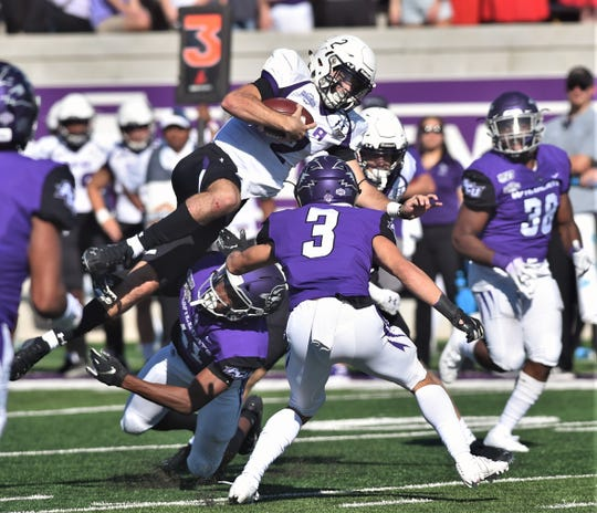 SFA quarterback Trae Self (2) tries to leap for a first down on a third-and-long play in the second quarter as Alex Lofton (bottom) and Ryan Stapp (3) defend. The play came up short of the first down during the Southland Conference game Saturday, Oct. 19, 2019, at Wildcat Stadium.