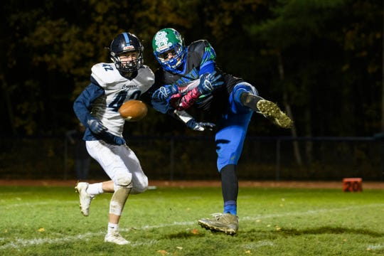 Colchester's Mitch Gadapee (99) tries to catch the pass as he's guarded by MMU's Matthew Reinfurt (42) during the high school football games between the Mount Mansfield Cougars and the Colchester Lakers at Colchester High School on Friday night October 18, 2019 in Colchester, Vermont.