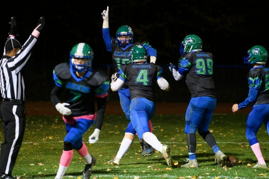 Colchester's Charlie Cusson-Ducharme (19) celebrates after intercepting the pass and scoring a touchdown during the high school football games between the Mount Mansfield Cougars and the Colchester Lakers at Colchester High School on Friday night October 18, 2019 in Colchester, Vermont.