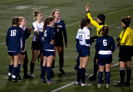 Burlington High School girls soccer players react to receiving yellow cards during Friday night's game against South Burlington at Buck Hard Field.