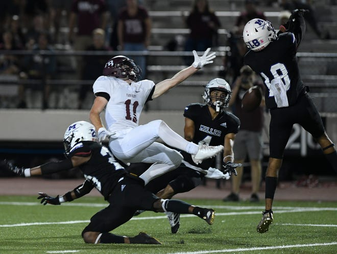 Flour Bluff's Jackson Soward, center, reaches for the ball as Miller defenders try to intercept the pass, Friday, Oct. 18, 2019, at Buc Stadium. Miller won, 34-28.