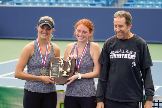 Indian Hills' Hayley Hirsch, Morgan Coburn, and coach Gary Samuels pose with their championship plaque after winning the division II doubles match at the Ohio girls tennis state tournament on Saturday, Oct. 19.