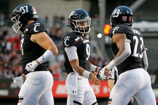 Cincinnati Bearcats quarterback Desmond Ridder (9) walks off after a touchdown run by running back Gerrid Doaks (23) in the fourth quarter of the NCAA American Athletic Conference game between the Cincinnati Bearcats and the Tulsa Golden Hurricane at Nippert Stadium in Cincinnati on Saturday, Oct. 19, 2019. The Bearcats became bowl eligible , improving to 6-1, with a 24-13 win at home.