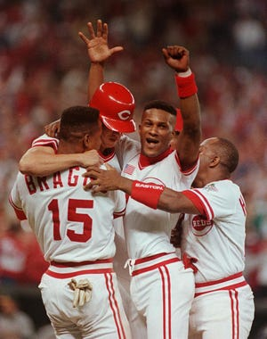 OCTOBER 17, 1990: Eric davis, center, celebrates with Reds teammates after a Bill Bates single scored Davis to win game two of the World Series against Oakland. Also shown are Glenn Braggs, Bill Bates and Billy Hatcher.