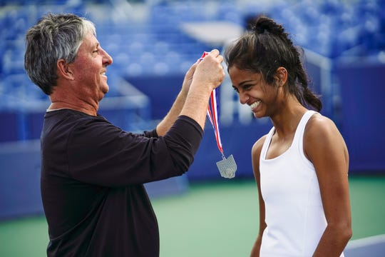 Mason coach Mike Reid presents Ananya Aggarwal with her second place medal after the division I singles championship match at the Ohio girls tennis state tournament on Saturday, Oct. 19.