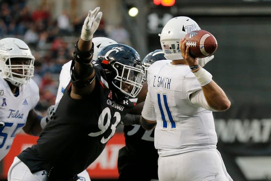 Cincinnati Bearcats defensive tackle Elijah Ponder (93) wraps up Tulsa Golden Hurricane quarterback Zach Smith (11) as he throws, forcing a bad throw and interception, in the fourth quarter of the NCAA American Athletic Conference game between the Cincinnati Bearcats and the Tulsa Golden Hurricane at Nippert Stadium in Cincinnati on Saturday, Oct. 19, 2019. The Bearcats became bowl eligible , improving to 6-1, with a 24-13 win at home.