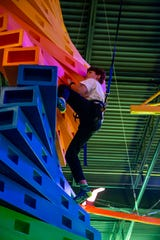 Ethan Mitchell, 13, of Waukee climbs a wall at Urban Air Adventure Park in Ankeny Friday, Oct. 18, 2019.