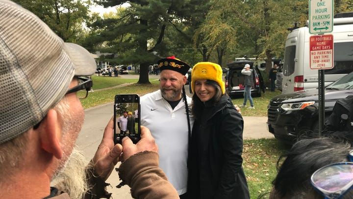 "Brian Decouster and U.S. Rep. Tulsi Gabbard pose for a photo in Iowa City after he gave the 2020 Democratic presidential candidate a Russian cossack hat as a joke referencing recent allegations that she is a ""Russian asset."""