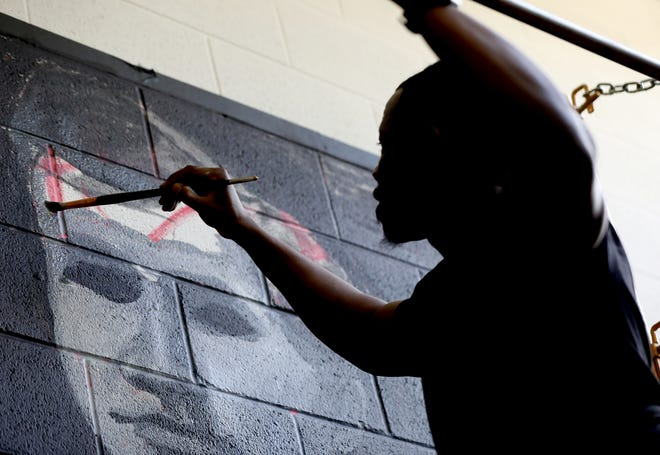 """Tylonn J. Sawyer, 42 of Detroit, works on the mural he's been painting inside the University of Michigan, Modern Languages Building on campus in Ann Arbor on Saturday, October 19, 2019. The mural titled """"First Man: Samuel Codes Watson (Acrylic)"""" is dedicated to the first African-American to attend the University of Michigan, Samuel Codes Watson.  In 1853, Samuel Codes Watson was the first African American student admitted to the Michigan."""