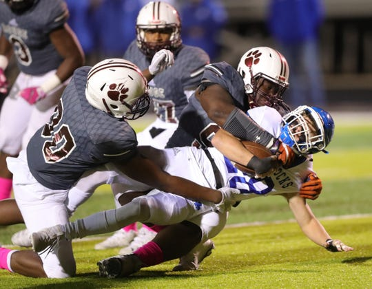 River Rouge high school defenders tackle Detroit Catholic Central's Danny Scott during first-half action Friday, Oct. 18, 2019 at River Rouge.