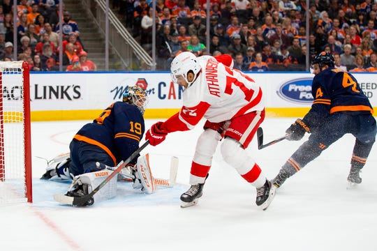 Edmonton Oilers goaltender Mikko Koskinen (19) makes a save against Detroit Red Wings center Andreas Athanasiou (72) during the first period of an NHL hockey game Friday, Oct. 18, 2019, in Edmonton, Alberta.
