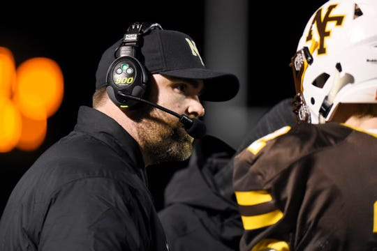 North Farmington head coach Jon Herstein talks to his players as they played against Farmington in the first quarter.