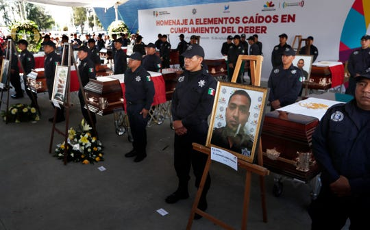 Michoacan state police stand next to the coffins of slain colleagues during an Oct. 15 memorial service at the public security department headquarters for Michoacan state, in Morelia, Mexico.