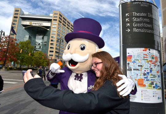 'Mr. Monopoly.' aka Marcus Goddard, of Detroit, poses for a selfie with Patience Moss, 13, of Franklin, Ohio. Ally Financial facilitates a Downtown Detroit Monopoly scavenger hunt where Mr. Monopoly is giving away prizes, including money, free food and drink vouchers and game tickets.