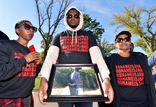 James White's daughter, Chanelle White, left, 27, and her aunt Mary Murray, both of Inkster, stand with Chanelle's brother, Joseph White, center, 25, of Wayne, as he holds a picture of their father, James White.
