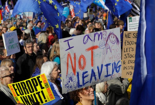 Anti-Brexit supporters carry signs and EU flags during a march in London, Saturday, Oct. 19, 2019.