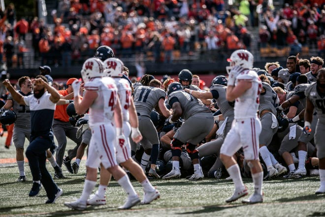 Wisconsin players walk off the field as Illinois celebrates their 24-21 win on Saturday.