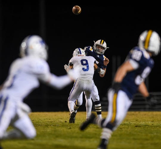 Castle's Cameron Tilly (15) passes the ball before getting hit by Memorial's Josh Russell (9) the Memorial vs Castle game at Castle High School's John Lidy Field, Newburgh, Friday, Oct. 18, 2019.