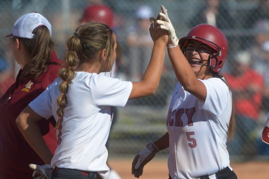 Rocky Mountain softball player Cora Aguirres, right, is high-fived after hitting a solo home run during a Class 5A regional title game against Cherry Creek on Saturday, Oct. 19, 2019. The Lobos won 4-2 to advance to the state tournament.
