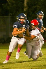 Gavin Smith of ECS tries to drag down Oasis running back Tanner Rennie during their game on Friday, Oct. 18, 2019, at Oasis High School.