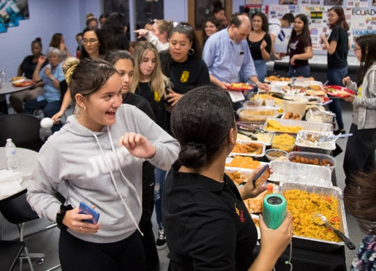 Students and teachers dance around the table of food during Multicultural Day at Mariner High School on Oct. 10, 2019, in Cape Coral.