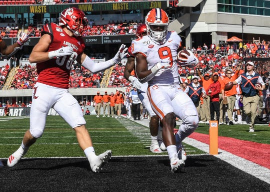 Clemson running back Travis Etienne (9) scores near  Louisville defensive back Jack Fagot(38) during the third quarter at Cardinal Stadium in Louisville, Kentucky Saturday, October 19, 2019.
