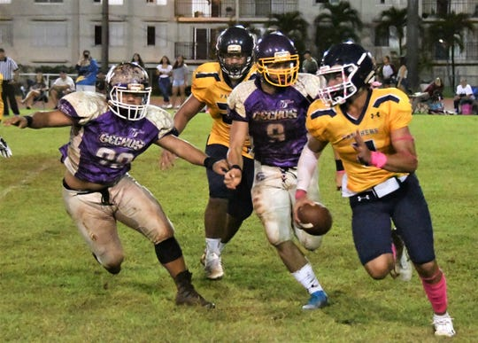 Guam High quarterback Travon Jacobs, right, is chased down by the Geckos defense including No. 9 William Rios in  semifinal playoff action against the GW Geckos Oct. 19 at GW field. The Geckos advanced to the title game with a 20-7 victory.