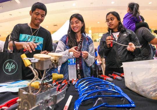 "Guam Community College electrical student Hazel Lazatin, center, share her knowledge of stripping and preparing electrical wiring with Tiyan High School sophomores, Davison Lanwi, left, and Ajann Kap, during the LIFE Teen Expo at the Agaña Shopping Center on Saturday, Oct. 19, 2019. The event, hosted by the Bank of Guam, was held to serve as ""a one stop resource for all teens"" to offer options for their post graduate needs, said Jackie Marati, BOG chief communications and corporate responsibliity officer."