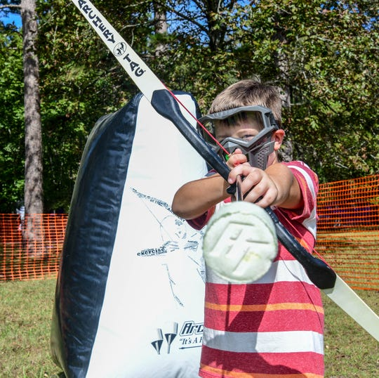 Canyon Collins holds an arrow in place during a game of archery tag at the Little Black Creek Campground in Lumberton, Miss., Saturday, Oct. 19, 2019.