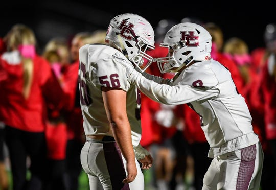 With the Panthers celebrating in the back ground, Henderson's Jackson Williams (56) and Henderson's Ben Dalton (8) react after losing to in overtime as the Henderson County Colonels play the Daviess County Panthers Friday evening at Reid Stadium, October 18, 2019.