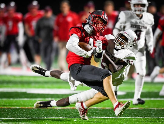 Henderson's Myekel Sanners (21) tries to pull down Daviess County's Bruno Espinosa (7) as the Henderson County Colonels play the Daviess County Panthers Friday evening at Reid Stadium, October 18, 2019.