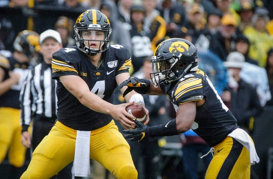 Nate Stanley, left, fakes a shotgun handoff to Mekhi Sargent. The Hawkeyes went with greater frequency of using the shotgun look with tight end Nate Wieting serving as a fullback of sorts against Purdue.