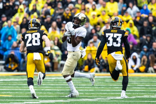 Purdue wide receiver David Bell (3) pulls in a pass in double coverage of Iowa defensive back Jack Koerner (28) and Iowa defensive back Riley Moss (33) during a NCAA Big Ten Conference football game between the Iowa Hawkeyes and Purdue, Saturday, Oct., 19, 2019, at Kinnick Stadium in Iowa City, Iowa.