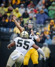 Iowa senior quarterback Nate Stanley gets rid of the ball as Purdue junior defensive end Derrick Barnes rushes forward in the third quarter on Saturday, Oct. 19, 2019, at Kinnick Stadium in Iowa City.