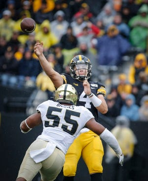 Iowa senior quarterback Nate Stanley gets rid of the ball as Purdue junior defensive end Derrick Barnes rushes forward in the third quarter on Saturday, Oct. 19, 2019, at Kinnick Stadium in Iowa City.