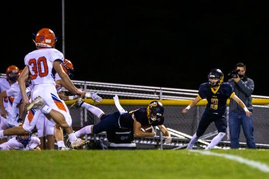 Iowa City Regina's Alec Wick (10) leaps for extra yardage during a Class 1A varsity football game, Friday, Oct., 18, 2019, at Regina Catholic High School in Iowa City, Iowa.